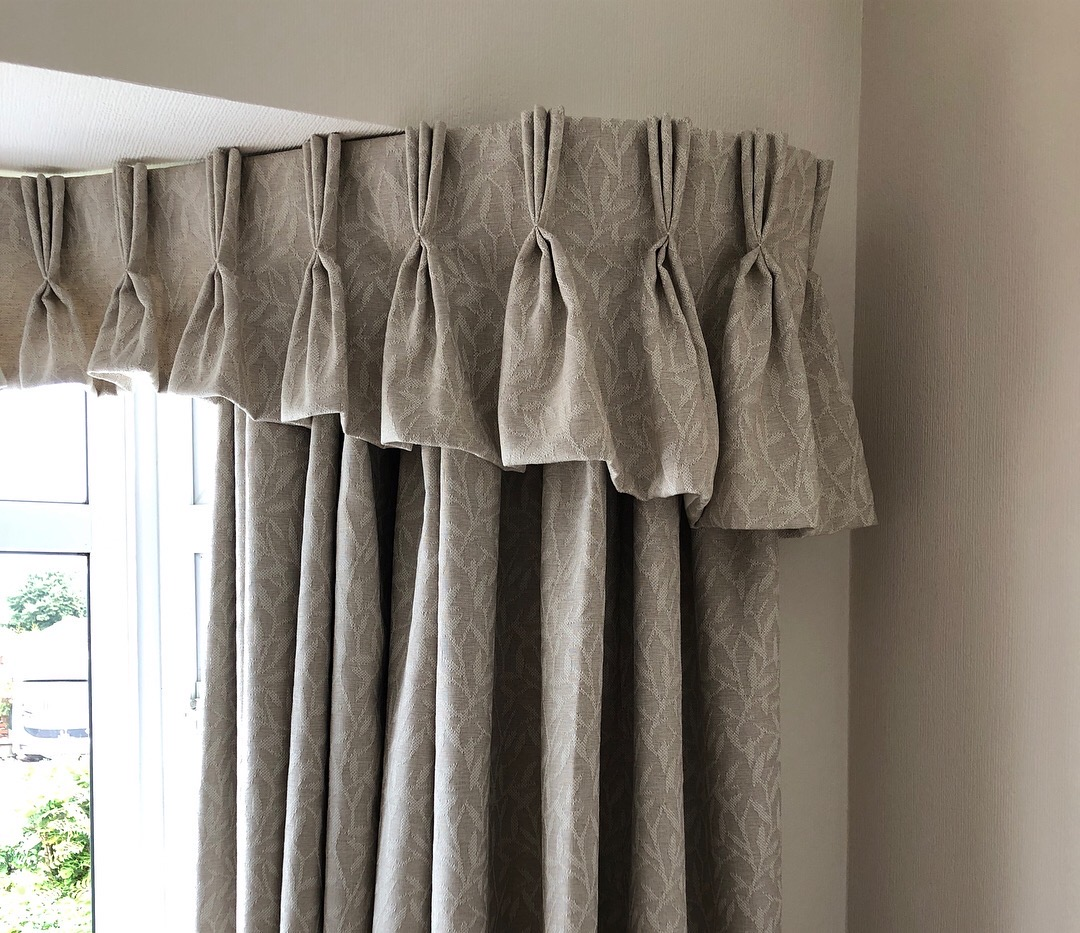 Triple pinch pleat shaped valance in a bay window